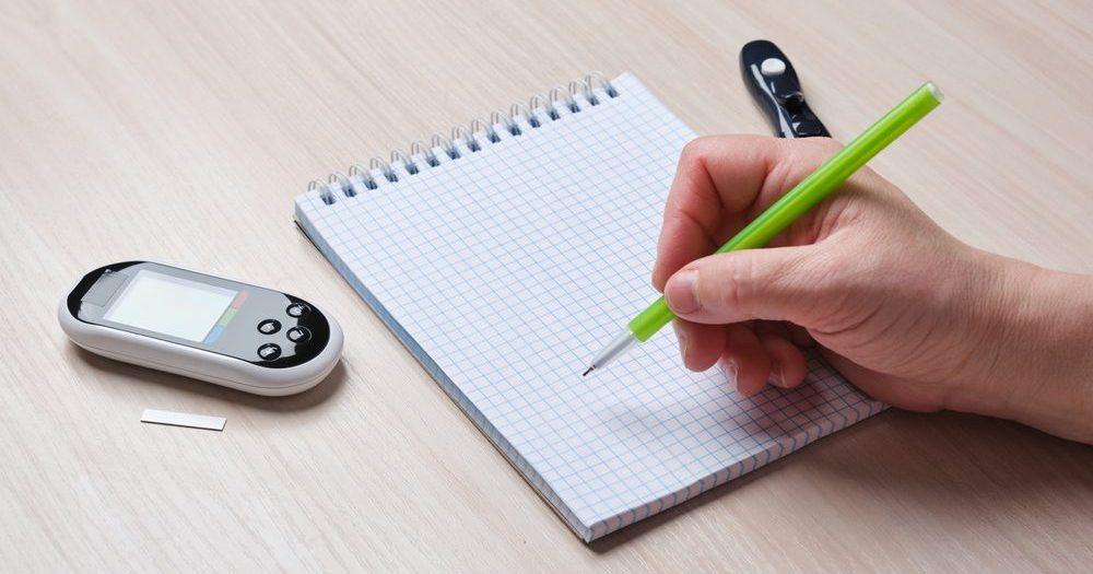 глюкометр, блокнот, ручка, рука