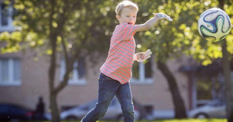 хлопчик грає з м'ячем