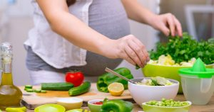 pregnant woman making salad